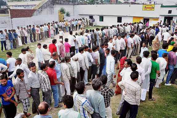 Voters stand in queue to cast their vote for Lok Sabha elections in Moradabad.