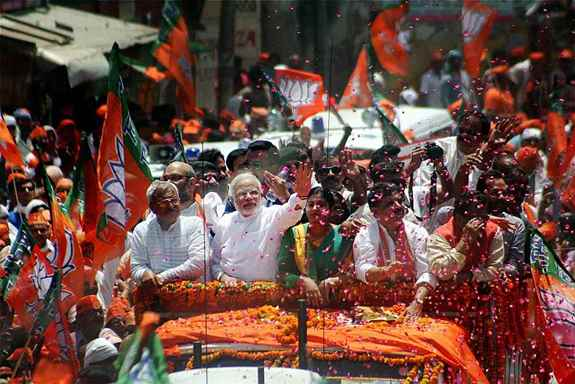 BJP Prime Ministerial candidate Narendra Modi waves towards supporters during a road show before filing his nomination papers in Varanasi.