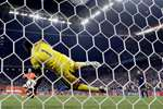 Argentina's goalkeeper Sergio Romero blocks a shot by Netherlands' Ron Vlaar during a penalty shootout after extra time during the World Cup semifinal match between the Netherlands and Argentina at the Itaquerao Stadium in Sao Paulo Brazil.