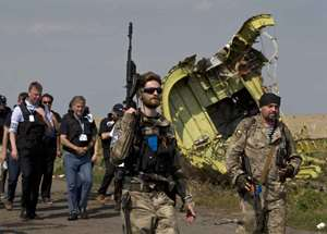 A pro-Russian rebel holds a gun passing by plane wreckage as members of the OSCE mission to Ukrainearrive for a media briefing at the crash site of Malaysia Airlines Flight 17, near the village of Hrabove, eastern Ukraine. A team of Malaysian investigators visited the site along with members of the OSCE mission in Ukraine for the first time since the air crash last week.