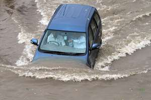 A car being driven through a waterlogged street in Ahmadabad.