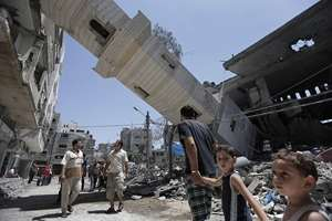 Palestinians inspect damage to adjacent houses from a fallen minaret of the Al-Sousi mosque that was destroyed in an Israel strike, at the Shati refugee camp, in the northern Gaza Strip.
