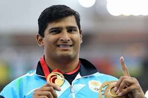 Vikas Shive Gowda of India holds up his gold medal for the men's discus throw following the medal ceremony at Hampden Park Stadium during the Commonwealth Games 2014 in Glasgow, Scotland.