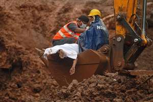 Rescuers recover a body from the site of a landslide in Malin village, in Maharashtra.