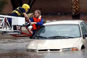 Tucson Fire Department personnel rescue a woman stranded in rising flood waters in east Tucson, Arizona.