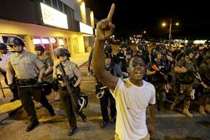 A man is moved by a line of police as authorities disperse a protest in Ferguson, Mo.