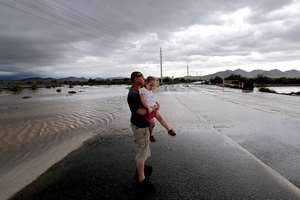 Josh Groves and his daughter Abagayle Groves, 3, wait to cross the road as flash flood waters overrun Skunk Creek through the Sonoran Desert, in northwestern Phoenix.
