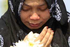 A Muslim woman cries as she waits outside Bunga Raya Complex at Kuala Lumpur International Airport before victims' bodies of the ill-fated Malaysia Airlines Flight MH17 are flown back, in Sepang, Malaysia. The bodies and ashes of 20 Malaysians killed when Malaysian Airlines Flight 17 was shot down over Ukraine in July have arrived in Kuala Lumpur.