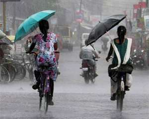 Girls use umbrellas while going to school in rains in Jalpaiguri.