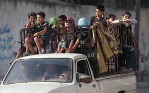 Palestinians with their belongings drive back to their homes in Gaza City's Shijaiyah neighborhood.