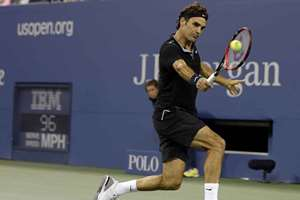 Roger Federer of Switzerland returns a shot to Marinko Matosevic of Australia during the first round of the 2014 U.S. Open tennis tournament in New York.