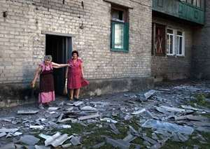 Local residents stand near the building where they live after a shelling in Donetsk, eastern Ukraine. Two columns of Russian tanks and military vehicles fired Grad missiles at a border post in southeastern Ukraine, then rolled into the country as Ukraine's over matched border guards fled, a top Ukrainian official said.