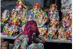 A vendor awaits customers as she sells idols of Ganesh on the first day of the Ganesh Chaturthi in Jammu