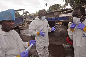 Liberian health worker prepare their protective gear before removing the body of a man that they believe died from the Ebola virus in Monrovia.