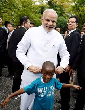 Prime Minister Narendra Modi shares a light moment with a child during his visit  at Golden Pavilion,  Buddhist temple in Kyoto Japan.