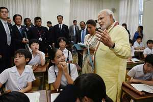 Prime Minister Narendra Modi interacts with students during a visit to Taimei Elementary school in Tokyo.