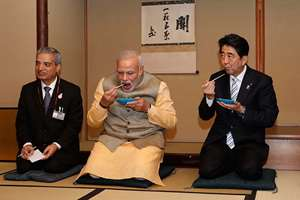 Prime Minister Narendra Modi, center, and Japanese Prime Minister Shinzo Abe, right, eat tea cakes during a tea ceremony at a tea hut of the Omotesenke, one of the main schools of Japanese tea ceremony, in Tokyo.