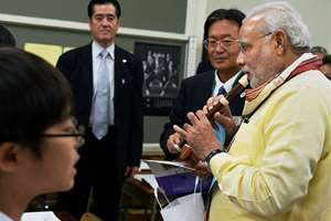 Prime Minister Narendra Modi tries a Japanese flute during a visit to Taimei Elementary school in Tokyo.