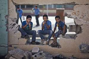 Children sit on a damaged wall of a school in Gaza City's Shijaiyah neighborhood.