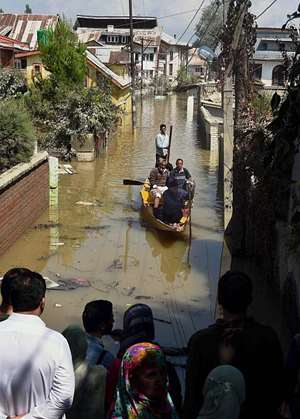 A boat carries relief material in a flooded street at Jawahar Nagar in Srinagar