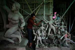 A craftsman works on statues of gods and goddesses for the upcoming festival of Durga Puja at a workshop in Guwahati.