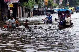 People wade through a waterlogged road after heavy rains at Rajendar Nagar in Patna.