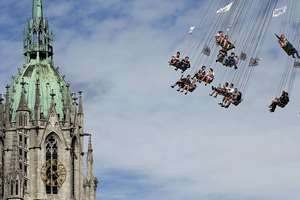People ride a merry-go-round in front of St. Paul church at the 181st Oktoberfest beer festival in Munich, southern Germany. The world's largest beer festival will be held from Sept. 20 to Oct. 5, 2014.