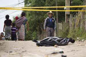 A resident pauses to look at a taped off area, where a body lies wrapped in a black bag, in Pajoques, Guatemala. An argument over plans to build a factory and highway in the village west of Guatemala City provoked a violent clash late Friday that has left at least six people dead and dozens of others seriously wounded.