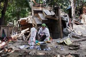 A woman hit by the Jammu and Kashmir floods, salvages her belongings from the ruins of her collapsed house in Pulwama