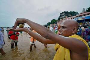 A devotee performs 'pindaan', a religious service for ancestors, on the banks of the sacred Falgu river in Gaya