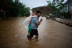A man carrying his son on his back wades through floodwaters in Guwahati, Assam.