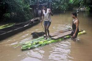 Villagers use a makeshift banana plantain raft to move across their flooded village at Bartezpur in Kamrup district of Assam.
