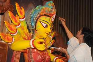West Bengal Chief Minister Mamata Banerjee gives final touches to eyes of an idol of goddess Durga, in Kolkata.