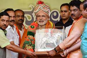 Prime Minister Narendra Modi being handed over a memento by state BJP leaders at a rally outside the HAL Airport in Bengaluru.