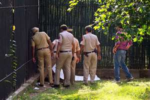 Policemen inspect the body of a man who was killed by a white tiger at the zoo in New Delhi.