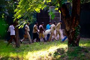 Workers carry the body of a man who was killed by a white tiger past its cage at the zoo in New Delhi.