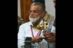 In this Nov. 5, 2013 file photo, Indian Space and Research Organization Chairman, K. Radhakrishnan, poses for the media with a model of the Mars orbiter after its successful launch at Sriharikota. With home-grown technology and a remarkably low budget of about $75 million, India could become the first nation to conduct a successful Mars mission on its first try.  If the Mars Orbiter Mission, or MOM, settles into orbit in the morning, Wednesday, Sept. 24, 2014 as planned, the country will join the U.S., European Space Agency and the former Soviet Union in the elite club of Martian explorers.