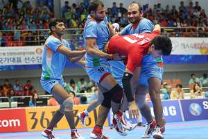 Thailand's Santi Bunchoet is caught by India team during the men's team kabbadi preliminary match at the 17th Asian Games in Incheon. India won 66-27.