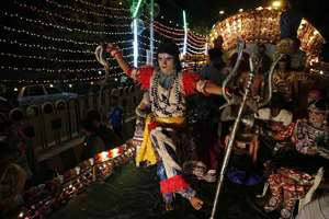 An artist dressed as Lord Shiva participates in a procession as part of Dussehra festival celebrations in Allahabad.