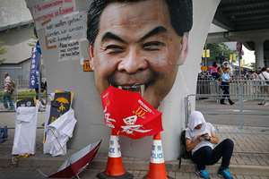A student protester rests next to a defaced cut-out of Hong Kong's Chief Executive Leung Chun-ying at one of their protest sites around the government headquarters, in Hong Kong.