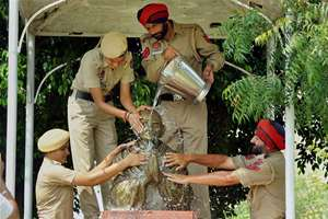 Punjab police personnel wash a Mahatma Gandhi statue on the eve of Gandhi Jayanti at Police Lines in Patiala.