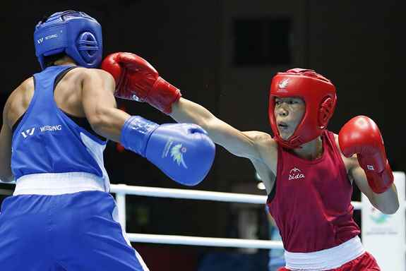 India's M.C. Mary Kom, right, and Kazakhstan's Zhaina Shekerbekova compete during the women's flyweight (48-51kg) final boxing match at the 17th Asian Games in Incheon, South Korea. Kom won the gold.