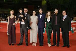 The cast, from left, actors Laura Sofia Bach, Yorick van Wageningen cradling young actor Ken Brady, Rinko Kikuchi, director Leonardo Guerra Seragnoli, actress Lucy Griffiths, actor Daniel Ball, and screenwriter Igor Tuveri, known as Igort, arrive for the screening of the movie Last Summer at the 9th edition of the Rome Film Festival Rome.