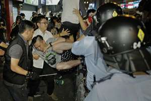 A pro-democracy protester is taken away by police offers at an occupied section of a roadway in the Mong Kok district of Hong Kong. Hong Kong riot police battled with thousands of pro-democracy protesters for control of the city's streets.