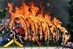 A member of Corps of Military Police Shwet Ashwa jumps through rings of fire during the platinum jubilee celebrations of their unit and affiliation ceremony of INS Kunjali at Dronacharya parade ground in Bengaluru.