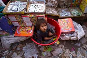 A small child is left inside the safety of a plastic bathing tub as his parents sell decorative artifacts in the middle of a busy market ahead of 'Diwali' festival, in New Delhi.