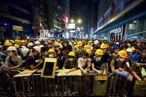 Protesters stand guard behind a barricade at the occupied area in the Mong Kok district of Hong Kong. Three weeks ago, students at a rally stormed a fenced-off courtyard outside Hong Kong's government headquarters, triggering unprecedented mass protests for greater democracy in the semiautonomous Chinese city.