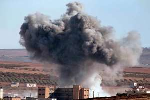 Thick smoke from an airstrike by the US-led coalition rises in Kobani, Syria, as seen from a hilltop on the outskirts of Suruc, at the Turkey-Syria border.