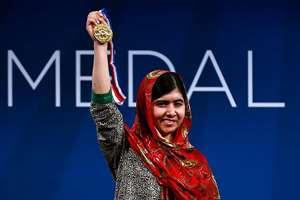 Malala Yousafzai holds up her Liberty Medal during a ceremony at the National Constitution Center, in Philadelphia. The honor is given annually to an individual who displays courage and conviction while striving to secure liberty for people worldwide.