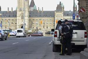 Police secure an area around Parliament Hill in Ottawa. A soldier standing guard at the National War Memorial was shot by an unknown gunman and people reported hearing gunfire inside the halls of Parliament. Prime Minister Stephen Harper was rushed away from Parliament Hill to an undisclosed location, according to officials.